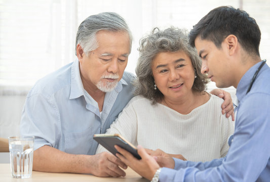 Elder senior old asian couple meeting  specialist professional caucasian doctor visit at home