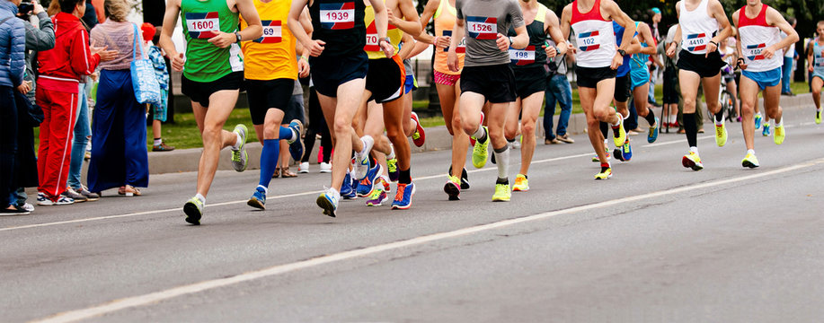 group runners athletes run marathon on city street