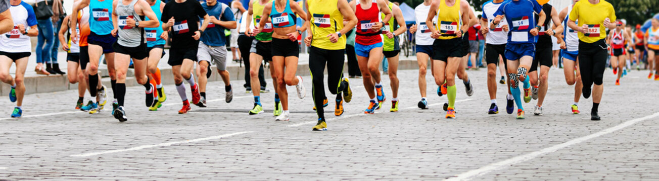 large group of runners athletes run city marathon on cobblestones
