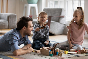 Happy little boy playing with toy dinosaur, having fun with smiling father and elder cute sister in living room. Joyful father enjoying playtime with small children siblings, lying on floor carpet.