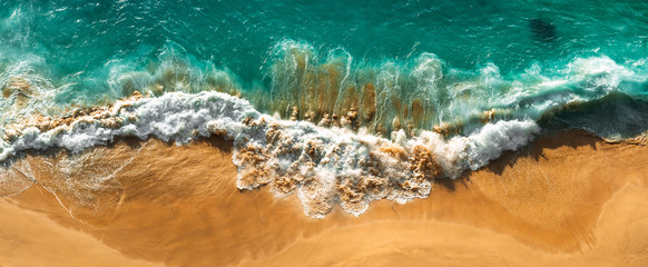 Fototapeta Aerial view of turquoise ocean waves in Kelingking beach, Nusa penida Island in Bali, Indonesia. Beautiful sandy beach with turquoise sea. Lonely sandy beach with beautiful waves. Beaches of Indonesia obraz