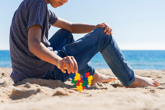 Autism awareness day concept. Boy teenager sitting on the beach with colorful puzzle autism awareness heart