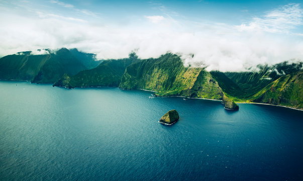 Beautiful Aerial View of Tropical Island Paradise Nature Scene of Maui Hawaii On Clear Sunny Day with Vibrant Blue Ocean Water and Waves and Lush Green Mountain Scenic Landscape with Big Rock in Sea