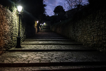 Dark medieval cobbled alley at night with several street lamps providing light