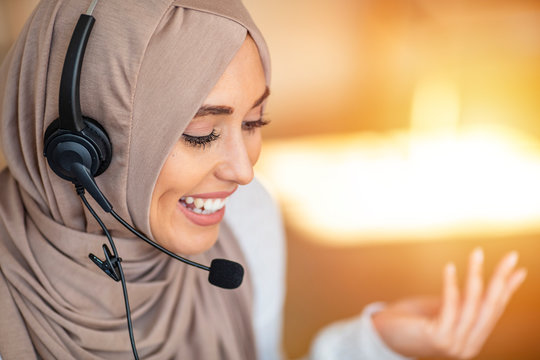 Portrait of happy young islamic woman in headscarf holding microphone and working on computer. Arab businesswoman working in customer service center talking using headset.