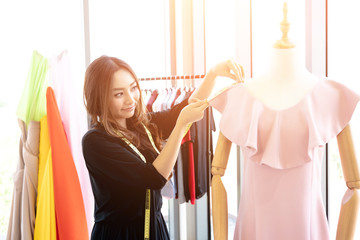 Happy smiling Asian creative fashion designer is working owner working in her tailor shop. Wall mural
