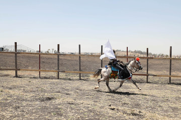 A man rides his horse next to the fence of the crash site during a memorial service for the victems of the Ethiopian Airlines Flight ET302 Boeing 737 Max plane crash near Bishoftu