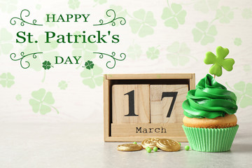 Delicious decorated cupcake, wooden block calendar and coins on light table. St. Patrick's Day celebration