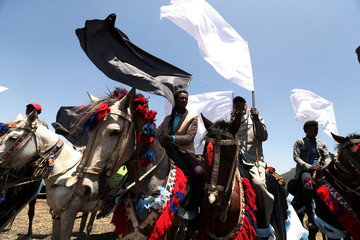 Men ride their horses next to the crash site during memorial service for the victims of the Ethiopian Airlines Flight ET302 Boeing 737 Max plane crash near Bishoftu