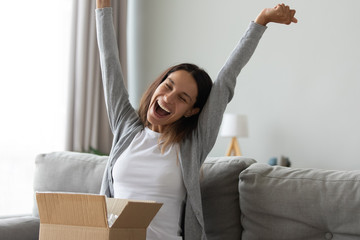 Overjoyed millennial Caucasian girl feel excited unpacking cardboard delivery box with Internet order shopping online, happy young woman triumph with good quality product buying things on web
