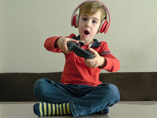 Child with headphones playing the console sitting at the table