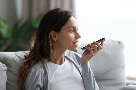 Young Caucasian woman sit on couch in living room using smartphone activate virtual digital assistant, millennial girl record voice message on modern cellphone gadget, new technology concept