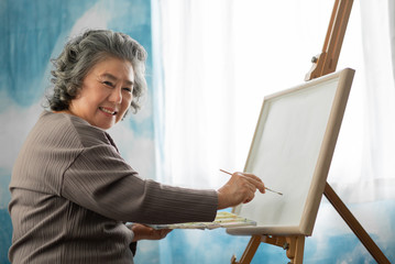 Happy smiling Asian Elderly woman oil painting on canvas at house on holidays.