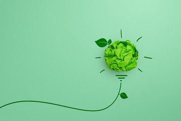 Green crumpled paper light bulb on green background, Corporate Social Responsibility (CSR),...