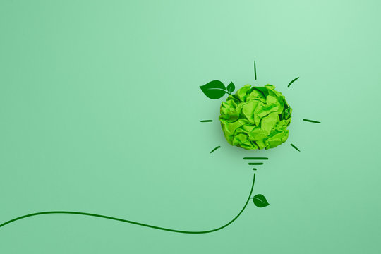 Green crumpled paper light bulb on green background, Corporate Social Responsibility (CSR), eco-friendly business and environmental concept