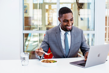 Portrait of a happy smiling young man in business suit eating lunch at work at his desk while working  on laptop computer in his office