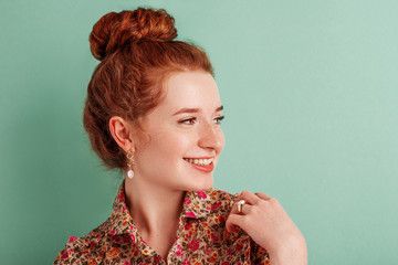 Happy smiling fashionable redhead girl wearing trendy pearl earrings, ring, floral print blouse, posing against green mint color background. Copy, empty space for text Wall mural