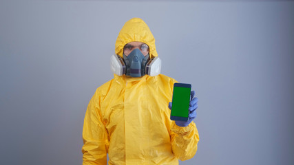 A man in yellow Hazmat suits and a respirator holds a phone with a green screen , gray background.