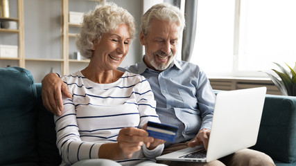 Smiling elderly husband and wife sit on couch make purchases on internet use bank credit card, happy modern middle-aged 60s couple customers shopping paying online on laptop at home