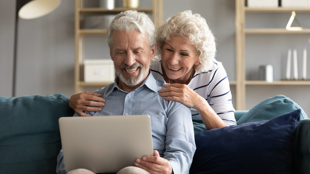 Happy elderly 50s husband and wife relax on comfy couch in living room watch funny video on laptop together, smiling old 60s couple rest on sofa at home have fun using modern computer gadget