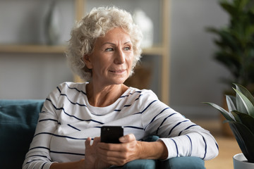 Happy old 50s woman sit on couch at home using modern cellphone gadget look in distance thinking, smiling middle-aged 60s female relax in living room with smartphone dreaming or visualizing