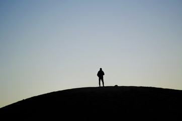 Silhouette of a person placed in the middle of a hill during a sunrise Wall mural