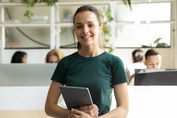 Portrait of smiling millennial Caucasian girl graphic designer pose holding modern tablet, profile picture of happy young female employee worker stand with pad in coworking office, internship concept