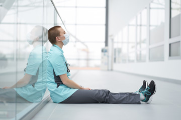 Burnout concept. Exhausted caucasian female short haircut doctor, wearing medical mask, sitting on a floor in corridor of clinic with closed eyes
