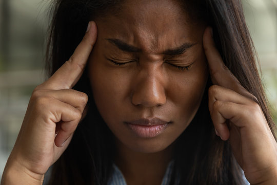 Unhealthy African American girl touch massage temples suffer from headache or migraine at workplace, tired biracial woman employee struggle with dizziness or blurry vision, overwork, fatigue concept
