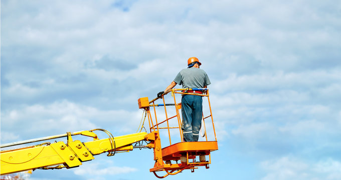 Worker in cherry picker bucket at height wearing hardhat and safety harness. Height construction worker against blue sky. Electrician standing in mobile crane bucket and rising to repair street wiring
