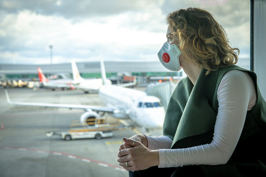 Woman with a mask on her mouth protects against the virus. She looks sad through the window at the airport on planes. Aerial connections canceled due to a coronavirus