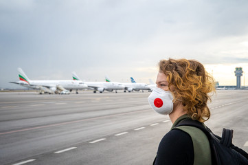 Woman with a mask on her mouth protects against the virus. Sadly looks at the aircraft parked at the airport. Canceled flights due to coronavirus Fotomurales