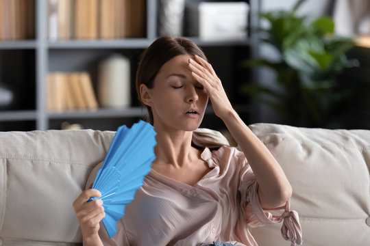 Head shot stressed unhealthy young woman using paper fan, suffering from heat stroke at home. Unhappy 30s lady sit on sofa, feeling high temperature indoors without air conditioning in living room.