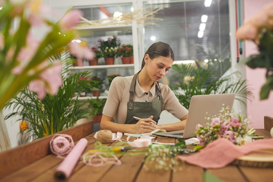 Portrait of female small business owner managing accounting books while using laptop at table in flower shop, copy space