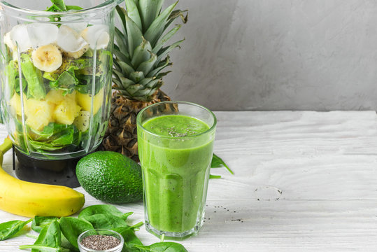Glass of green smoothie detox with fresh juicy ingredients in blender for making healthy drink