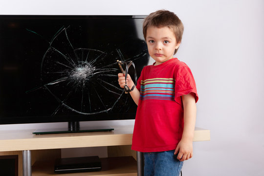 Frightened little boy standing in front of a TV with broken screen holding a slingshot