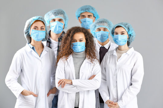 Group of doctors with protective masks on grey background. Concept of epidemic