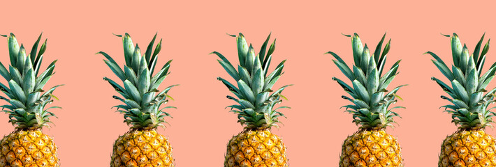 Many pineapples on a solid color background