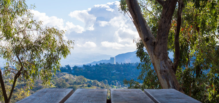 wooden picnic table overlooking lush forests and hillsides in the Los Angeles basin under blue skies