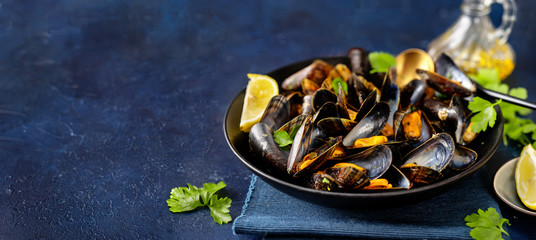 Close up of delicious steamed mussels in a plate on blue background