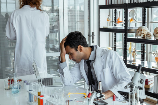Frustrated upset research scientists feeling tired worried with problem in chemical laboratory.