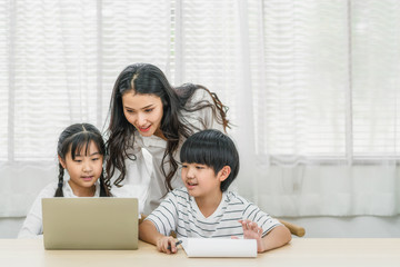 Young Asian Single Mother teaching or helping daughter and son doing home work with technology laptop in home, home school education, relationship and family, communication and conversation concept