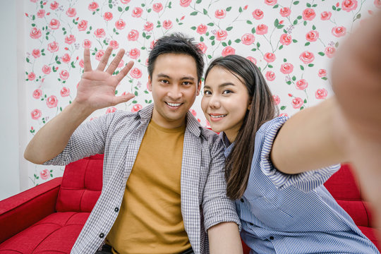 Asian Vlogger of married couple taking video and stream live to attendee via mobile phone by social media channel, say hello and bye bye, lovers and valentine, vlog and influencer freelance concept