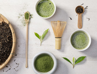 Organic matcha green tea powder in bowl with wire whisk and green tea leaf on white stone table, Organic product from the nature for healthy with traditional style