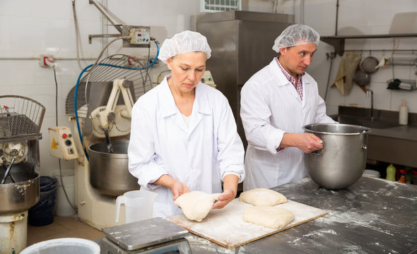 Man and woman prepare bread in the kitchen of the bakery