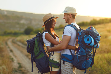 Couple hikers with backpack walking on hike in nature