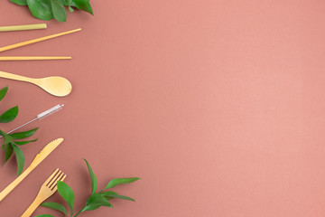 Frame made of bamboo cutlery and green leaves. Plastic free concept with copyspace on brown background. Wall mural