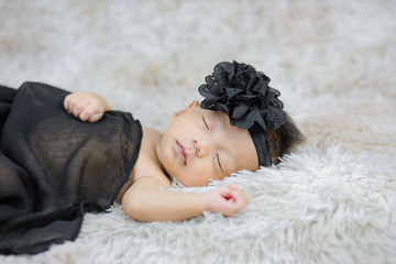 Fototapeta Close up cute Newborn wearing Flower headband on wool carpets, fashion concept