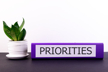 PRIORITIES word concept written on a folder lying on a dark table with a flower in a pot on a light background