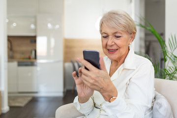 Mature woman with mobile phone on her hands sitting in room and sending messages to her friends and family. Senior woman texting on her mobile phone Fotobehang